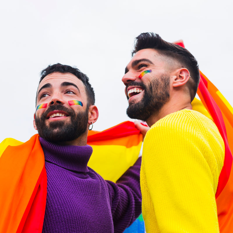 A young gay couple wrapped in a rainbow flag for Pride