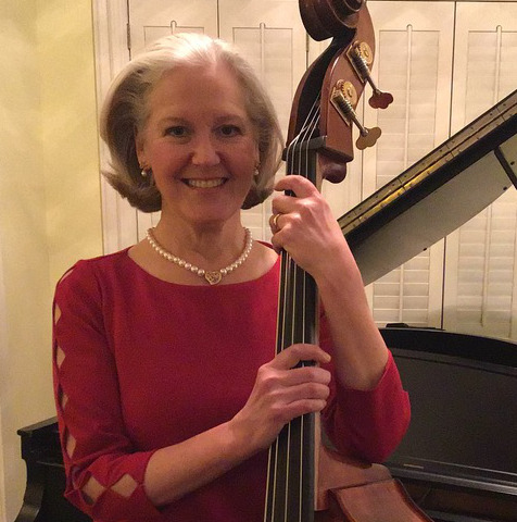 Elizabeth Smith Curtis Music Director holding a cello and looking at the camera