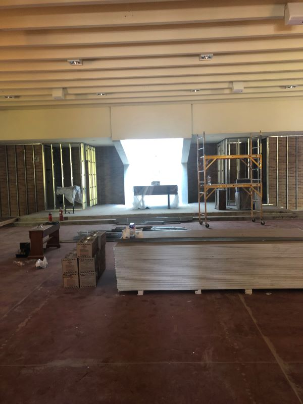 a room in the process of remodeling with stacks of lumber on the floor